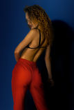 Gorgeous lady with curly hait in red pants. On blue background Royalty Free Stock Photo