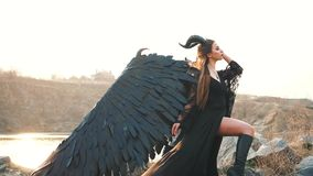 Gorgeous lady with dark soul, queen of night watching sunrise, girl in long light black dress with black feather wings
