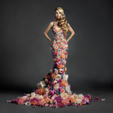 Gorgeous lady in dress of flowers. Studio portrait of blooming gorgeous lady in dress of flowers Stock Photography