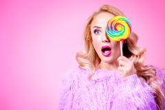 Gorgeous lady with lollipop. A portrait of a fashionable bright lady posing in studio with colorful lollipop. Fashion for women. Pink colors royalty free stock photography