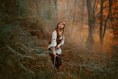 Gorgeous lady with long red hair in leather clothes follows wild animal, hunts down prey in rainforest, rite of. Initiation into hunters, girl pulled bowstring stock images