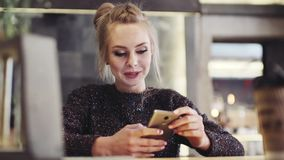 Gorgeous lady with natural makeup using her mobile phone. Modern devices. Being online, active lifestyle. Businesswoman. In the cafe. Close up view, slow motion stock footage