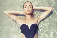 Gorgeous lady in seawater. Gorgeous young lady in a black swimsuit in seawater Royalty Free Stock Image