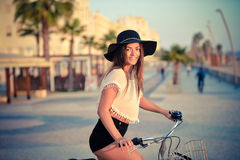 Gorgeous lady in sexy summer outfit riding bicycle Stock Photography