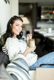 Gorgeous lady sipping coffee in a bar in a leisurly posture Royalty Free Stock Image