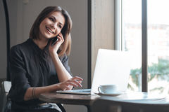 Gorgeous lady sitting at table in cafe talking by phone. Picture of gorgeous lady sitting at the table in cafe and using laptop while talking by phone. Look at Stock Images