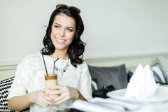 Gorgeous  lady smiling in a restaurant while holding her coffee Royalty Free Stock Photography