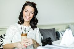 Gorgeous lady smiling in a restaurant while holding her coffee Royalty Free Stock Images