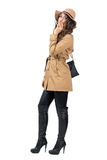 Gorgeous lady wearing coat, hat and handbag smoking cigarette side view Stock Image