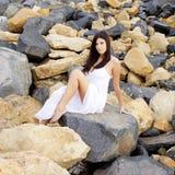 Gorgeous lady with white dress posing sitting on rocks smiling looking camera medium shot stock images