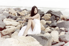 Gorgeous lady with white dress posing sitting on rocks smiling looking the ocean happy retro style stock photo