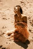 Gorgeous lady wth closed eyes in pink dress. Sits in a hot desert royalty free stock photos
