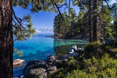 Tahoe`s clear, turquoise waters surrounTahoe`s clear, turquoise waters surrounded by pine forest aded by pine forest and mountains Stock Image