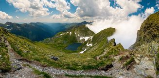 Gorgeous landscape of Fagaras mountains in summer. Clouds rising above the rocky cliffs. lake Capra down the grassy slope in the valley. view from the tourist stock image