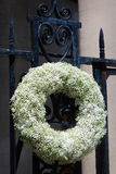 Gorgeous large white flowered wreath hanging on a black iron gate in downtown Charleston, South Carolina. Stock Photos