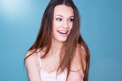 Gorgeous laughing playful young woman. With a beaming smile looking to the right of the frame, head and shoulders over blue Royalty Free Stock Images