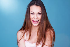 Gorgeous laughing playful young woman. With a beaming smile looking to the right of the frame, head and shoulders over blue Stock Image