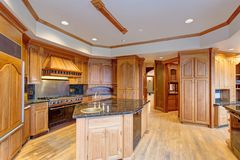 Gorgeous light filled mansion features an opulent kitchen. With rich wood cabinetry with marble countertops and an oversized kitchen  island Stock Images