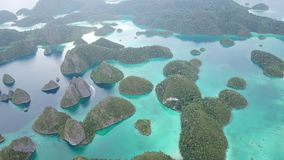 Amazing Tropical Islands and Lagoon in Wayag, Raja Ampat. The gorgeous limestone islands of Wayag, Raja Ampat, are surrounded by shallow coral reefs. This remote stock footage