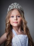 Gorgeous little girl in crown. On gray background Royalty Free Stock Images