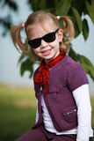 A gorgeous little girl with red scarf smiling in sunglases Royalty Free Stock Photo