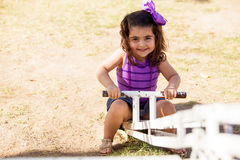 Gorgeous little girl in a seesaw Stock Image