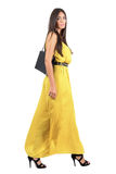 Gorgeous long hair beauty in evening dress walking side view Stock Images