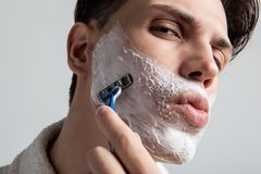 Gorgeous male is having morning skincare. Low angle close up of youthful man is standing and shaving stubble on his cheeks using personal razor. He is looking at Stock Photos