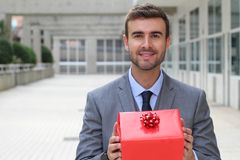 Gorgeous male holding a red present royalty free stock photography