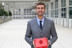 Gorgeous male holding a red present with copy space stock photography