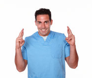 Gorgeous male nurse crossing his fingers Stock Photography