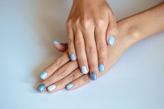 Gorgeous manicure, pastel tender blue color nail polish, closeup. Female hands over simple background. Gorgeous manicure, pastel tender blue color nail polish royalty free stock photo