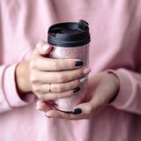 Gorgeous manicure, pastel tender pink color nail polish, closeup photo. Female hands hold a plastic coffee cup. Over simple background stock photo