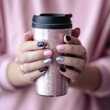 Gorgeous manicure, pastel tender pink color nail polish, closeup photo. Female hands hold a plastic coffee cup. Over simple background stock image