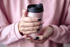 Gorgeous manicure, pastel tender pink color nail polish, closeup photo. Female hands hold a plastic coffee cup. Over simple background stock photos