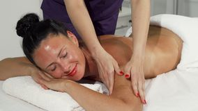 Beautiful happy mature woman smiling while enjoying back massage. Gorgeous mature women smiling to the camera, getting relaxing massage at luxurious spa center stock image