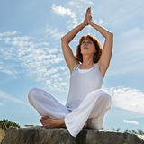 Gorgeous mature yoga woman exercising in lotus position outdoors Royalty Free Stock Photos