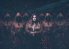 Gorgeous menacing femme fatale in the image of a mysterious priestess standing in a group, masks on their faces and. A girl servant wanders around with candles royalty free stock photos