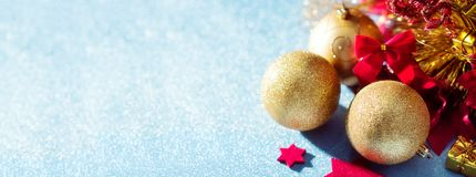 Gorgeous metallic gold christmas baubles, red stars and wrapped present on shiny blue background. Christmas banner. Gorgeous metallic gold christmas baubles stock images