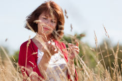 Gorgeous middle age woman thinking in high dry field flowers Royalty Free Stock Photos