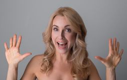 Gorgeous middle-aged female is feeling content. Sensation. Portrait of attractive overjoyed naked woman is standing with opened mouth and showing her palms to royalty free stock photo