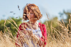 Gorgeous middle aged woman wandering in dry high meadows. Outdoors relaxation - gorgeous middle aged woman enjoying quietness,wandering in dry high meadows Royalty Free Stock Image
