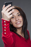 Gorgeous mixed-race young woman smiling for her self-portrait on cell phone Stock Photography