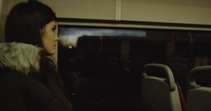 Gorgeous model closeup daydreaming on a bus. A young woman looks out the window on the bus. 4k stock footage