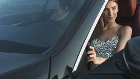 Gorgeous model in the strapless dress posing with the expensive car. Outdoors stock footage