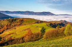 Gorgeous morning in mountainous rural area. In autumn. wooden fence along the grassy rolling hills with hay stacks fall in to the valley with thick rising fog Royalty Free Stock Photography