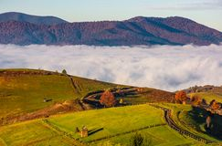 Gorgeous morning in mountainous rural area. In autumn. wooden fence along the grassy rolling hills with hay stacks fall in to the valley with thick rising fog Stock Photography