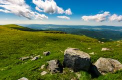 Gorgeous mountain landscape on a summer day. Giant boulders on a grassy hillside under the beautiful sky with clouds stock photo