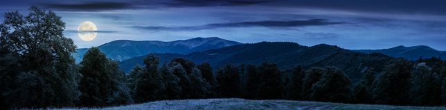 Gorgeous mountain panorama in summer at night. In full moon light. primeval beech forest around alpine meadow. distant ridge beneath the cloudy sky royalty free stock photography