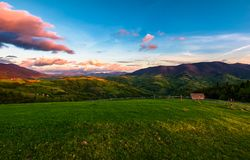 Gorgeous mountainous countryside at dusk. Beautiful landscape with rural fields, fence and woodshed. pink clouds on a spring blue sky over the mountain ridge royalty free stock photos